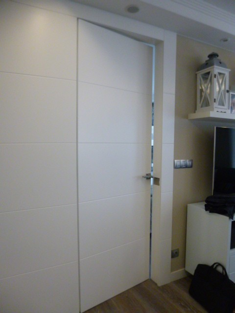 Detalle de la puerta enrasada con la pared panelada